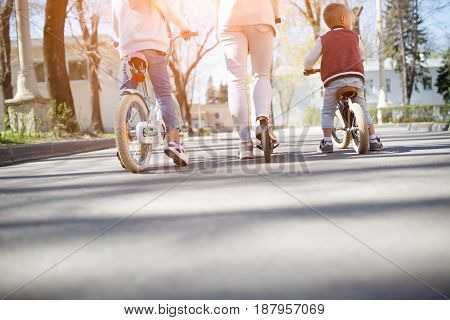 Family on bike ride in park. Photo from below