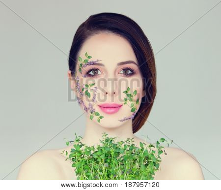portrait of beautiful young woman with flowers on her face holding plant on the wonderful grey studio background