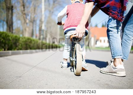 Man teaching boy to ride bike in park. Photo from back