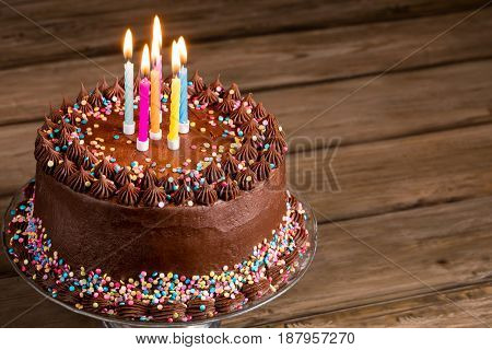 Chocolate birthday cake with sprinkles and candles