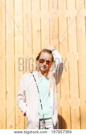 Young blonde at wooden wall on street during day