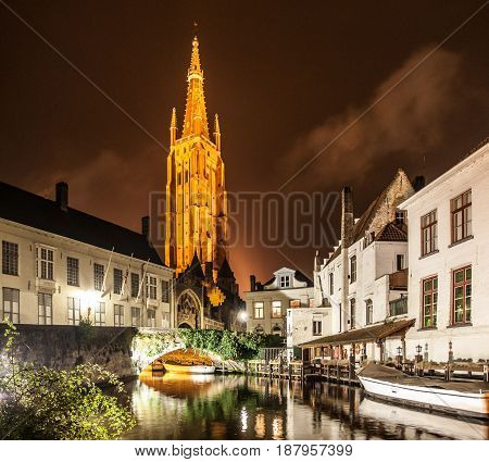 Church of Our Lady and bridge over water canal by night, Bruges, Belgium.
