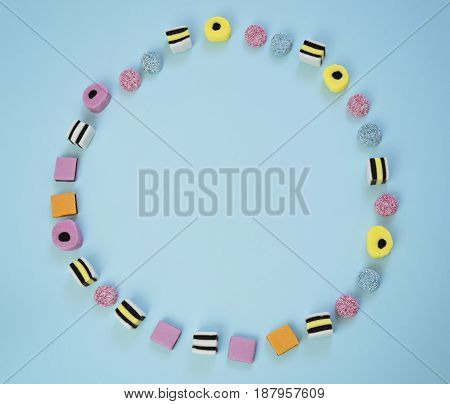 Chewing jelly colored candy lined in the shape of a ring on the blue background, abstract concept, copy space