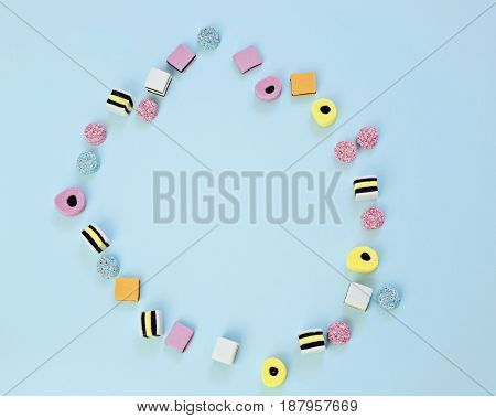 Colored jelly sweets are scattered on the blue background in the shape of a ring