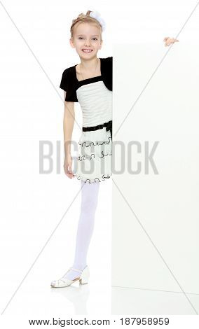 Beautiful little blonde girl dressed in a white short dress with black sleeves and a black belt.The girl peeks out from behind white banner.Isolated on white background.