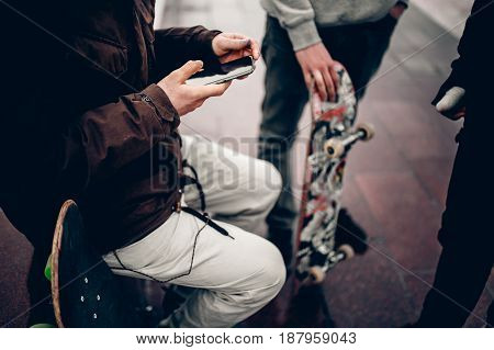 guy is holding the phone on the background Friends of the company of men holding their hands skateboards. Concept group of street athletes students social network