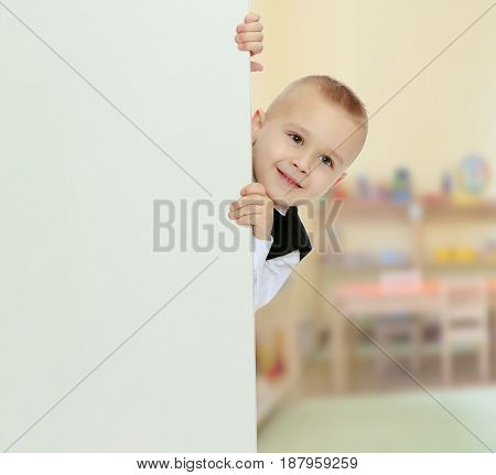 Cute little blonde boy in a black waistcoat and a white shirt and a bow at the neck , peeping over white banner.In the Montessori room the children's garden where there are shelves with toys and material.
