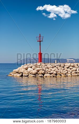 Beautiful seascape with lighthouse. Calm sea and a lighthouse on the pier. Red white solitary pulp