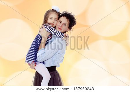 Happy young beautiful mother, lifted his little beloved daughter .And the girl embraced her mother's neck and pressed my face to her cheek.Brown festive, Christmas background.