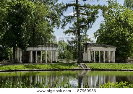 Beautiful landscape scaling in a public park near a lake ancient ruins of a column