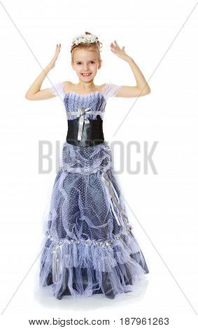 Adorable little blond girl dressed in long Princess dress.A girl tries on a head a diadem.Isolated on white background.