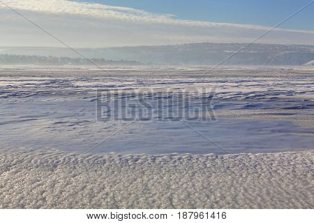 winter landscape with frozen lake and snowy hills