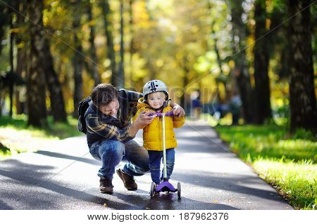 Middle age father showing his toddler son how to ride a scooter in a autumn park. . Active family leisure. Child in helmet. Safety sports leisure with kids concept.