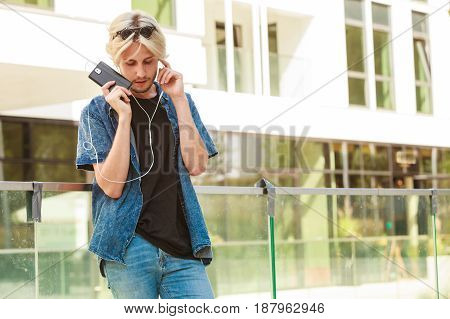 Hipster Man Standing With Earphones Talking On Phone