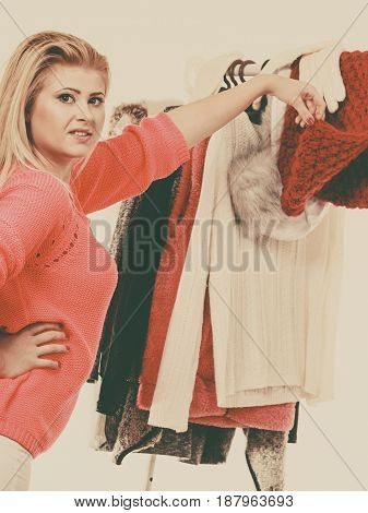 Woman In Home Closet Choosing Clothing
