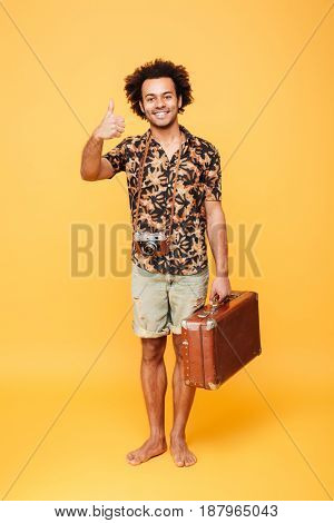 Full length portrait of a happy joyful african man holding suitcase and showing thumbs up isolated over yellow background