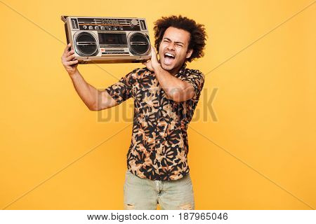 Picture of young screaming african man standing with tape recorder isolated over yellow background.