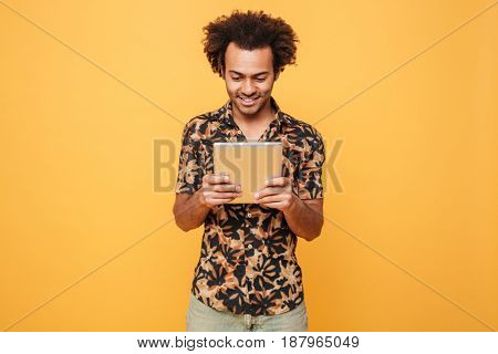 Portrait of a smiling young afro american guy standing and using pc tablet isolated over yellow background
