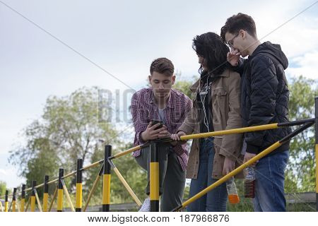 Two Boys And A Girl Standing On The Street  And Looking At The Mobile Phone