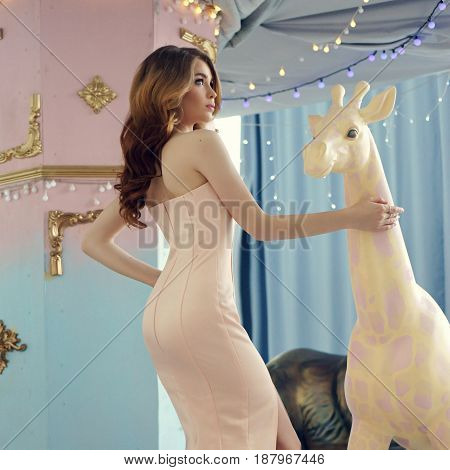 Fashion vogue style portrait. Elegant lady with red curly hair in pink mermaid dress at carousel.