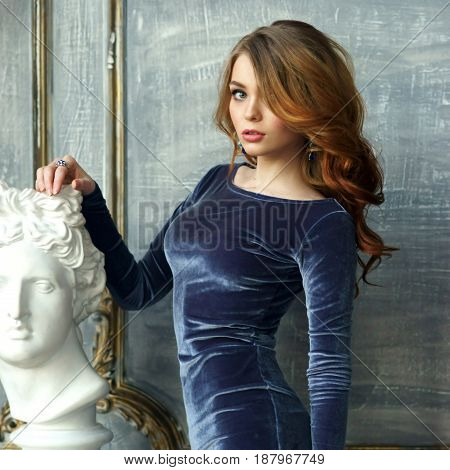 Fashionable portrait of young red hair woman in blue dress standing in luxury interior