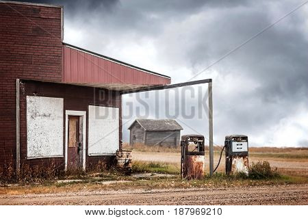 horizontal image of a very old abandoned gas station with two rusty broken down gas pumps under a dark cloudy thunder storm.