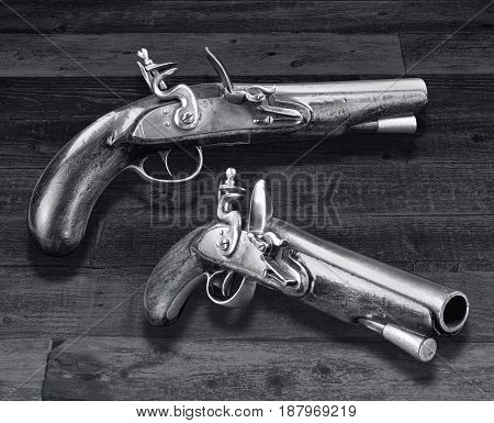 Antique English flintlock pistols made in the late 1700's in black and white.