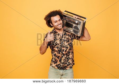 Image of young smiling african man standing with tape recorder isolated over yellow background. Looking at camera showing thumbs up.
