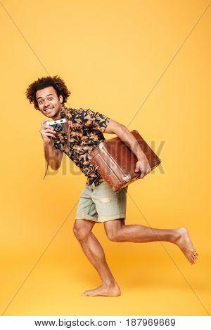 Image of young smiling african man running with suitcase isolated over yellow background. Looking at camera.