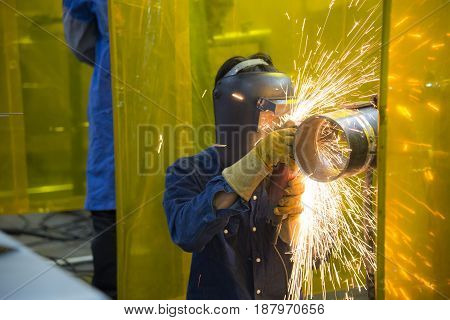 The welding craftsman grinding the steel tube and ware the safety mask.Safety working concept