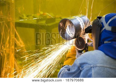 The welding crafstman grinding the steel tube and ware the safety mask.Safety working concept