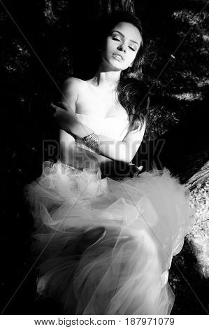monochrome fashion portrait of young beautiful tender woman in white dress lying on the tree with closed eyes