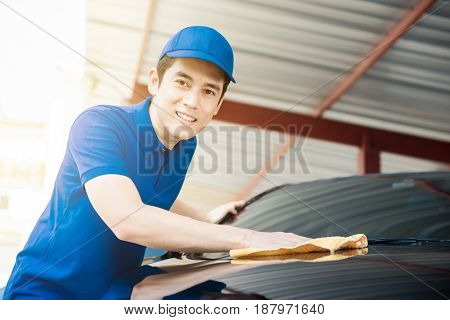 A man polishing (cleaning) car in the garage car detailing or valeting concept