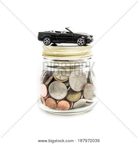 Toy car on the glass jar full of money (coins) - auto financial concept