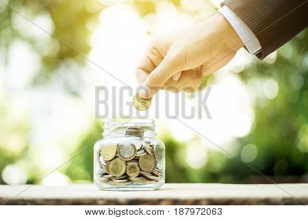 Businessman hand putting money (coin) into the glass jar - savings investment and donation concepts