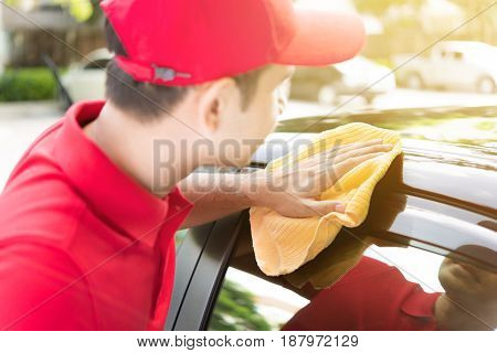 A man cleaning car - auto detailing and valeting service concept