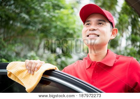Smiling auto service staff thinking(daydreaming) while cleaning car door