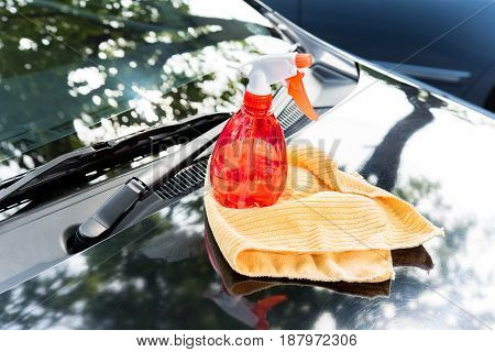 Cleaning equipments spray bottle and microfiber cloth on car bonnet