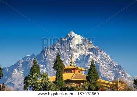 Mount Pandim 6691 mtrs 21952 feet high one of the highest peaks of Himalayan Mountain range - with top of Rinchenpong Monastery in foreground clear blue sky above. Rinchenpong Sikkim India