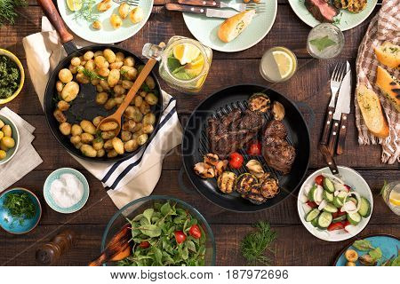 Dinner table with grilled steak grilled vegetables potatoes salad different snacks and homemade lemonade top view