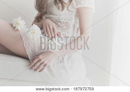 Lovely girl holding white flowers in her lap. She is wearing a white dress. The bride is waiting for the ceremony. Man is unrecognizable.