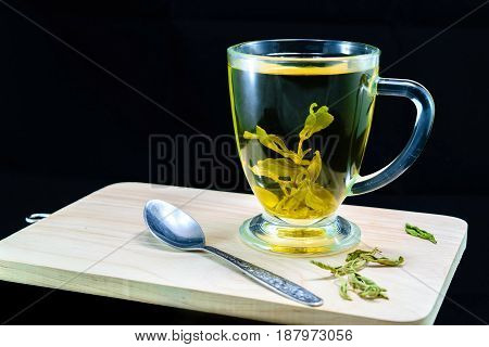 A cup with stevia infusion with spoon steel on wooden bord on black background