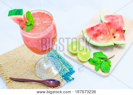 Watermelon smoothies with lime and mint on white background