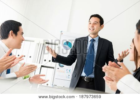 Colleagues giving an applause to a meeting leader while he is making a presentation