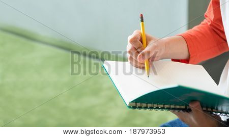 Close up hand of male teenager writing with pencil on notebook at campus universityEducation concpetleave space at left to adding text.