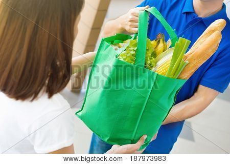 Delivery man giving grocery bag to a woman - food shopping service concept