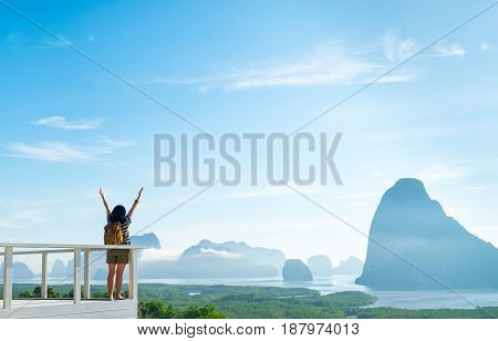 Happy young traveler woman backpacker raised arm up to sky enjoying a beautiful of nature at mountain panorama view point and seaFreedom wanderlustKhao Samed Nang Chee ViewpointPhang NgaThailand