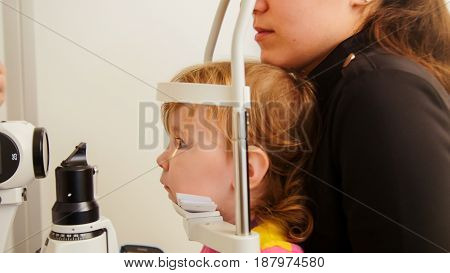 Eye clinic - small hild's eyesight checked on the ophthalmologic apparatus