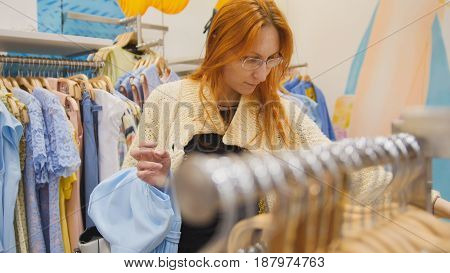 Shopping for women - beautiful red-haired girl chooses a summer dress