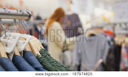 Shopping for women - hanger with blue and green dresses against the background of a beautiful woman